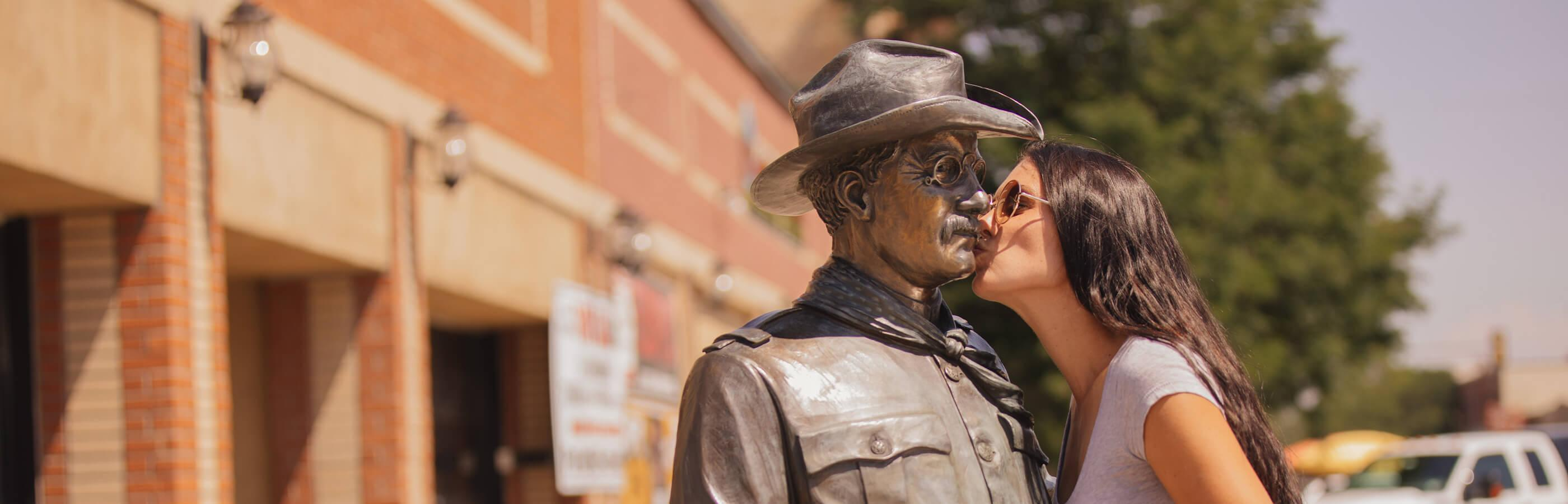 Woman kissing a Teddy Roosevelt statue from the City of Presidents