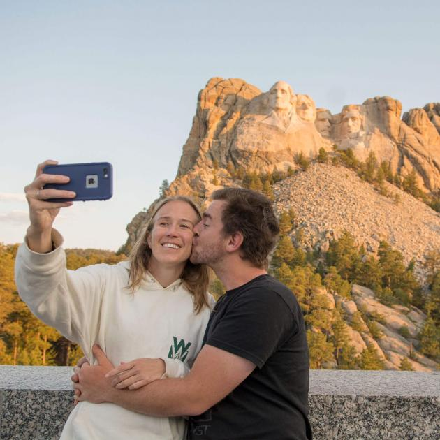 Couple taking photo in front of Mount Rushmore