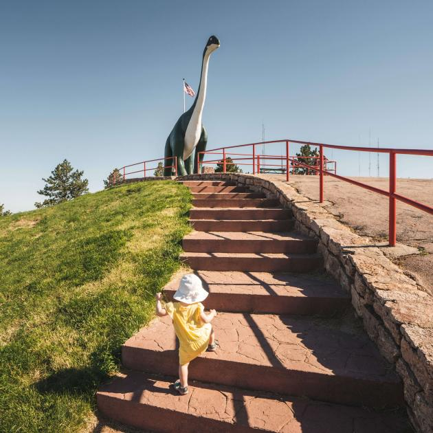 Little girl climbing the stairs to Dinosaur Park in Rapid City