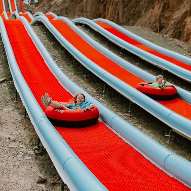 Kids racing on the tubing hill at Rushmore Tramway Adventures