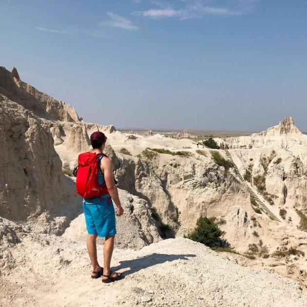 Hiker overlooking the ladder portion of Notch Trail in Badlands National Park