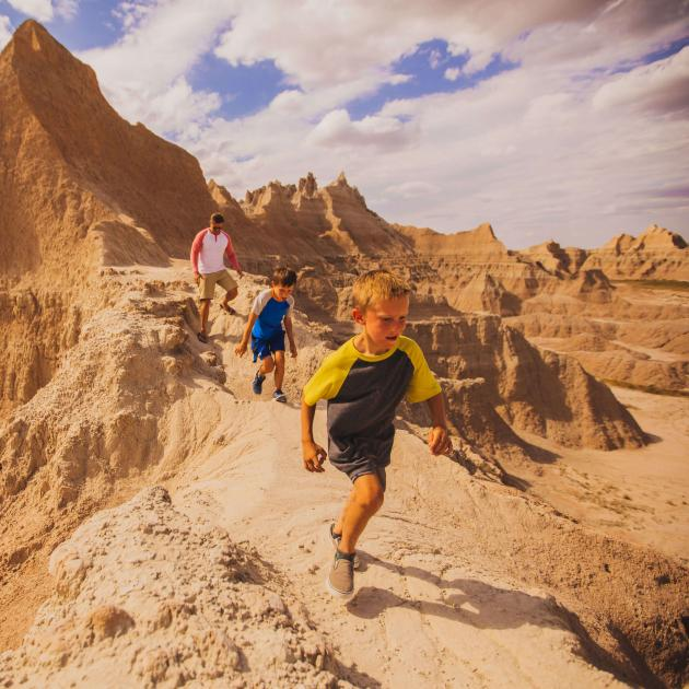 Family running through the Badlands in the summer